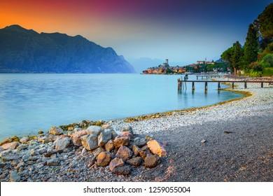 Fantastic recreation place, Malcesine touristic resort, amazing gravel beach and stunning sunset, Garda lake, Veneto region, Italy, Europe