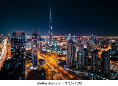 Fantastic rooftop view of Dubai's modern architecture by night with illuminated skyscrapers.