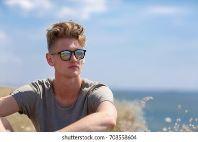 A fantastic, sassy young man with blond hair, in dark sunglasses relaxing on a sunny field background. A stylish hipster teenager in a loose shirt on a summer holiday. Copy space.