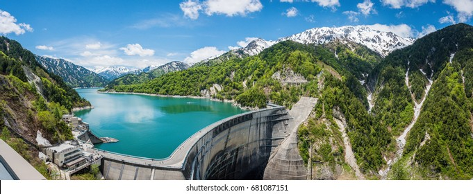 Fantastic scene on Kurobe dam. The dam between mountains with green lake at Kurobe dam, a part of Tateyama Kurobe Alpine route Murodo Daira, Japan. Large panorama photo
