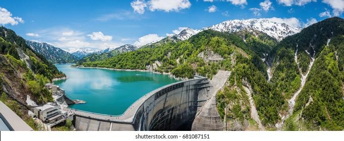 Fantastic scene on Kurobe dam. The dam between mountains with green lake at Kurobe dam, a part of Tateyama Kurobe Alpine route Murodo Daira, Japan. Large panorama photo