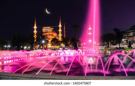 "Fantastic scenery with fountain and mahya among the Blue Mosque (Sultanahmet Camii) minarets at the starry night and bright moon. Text translation: ""Aid brings blessing"""