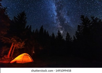 Fantastic starry night with galaxy Milky Way with a tourist and a tent on the mountain range in the Ukrainian Carpathians
