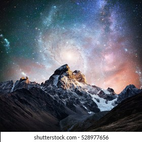 Fantastic starry sky. Snow-capped peaks. Main Caucasian Ridge. Courtesy of NASA. Mountain View from Mount Ushba Meyer, Georgia. Europe.