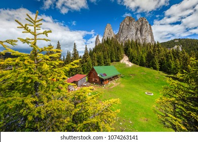 Fantastic summer alpine landscape, mountain chalet and high cliffs, Piatra Singuratica, (Lonely Rock), Hasmasul Mare mountains in Transylvania, Romania, Europe