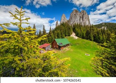 Fantastic summer alpine landscape, mountain chalet and high cliffs, Piatra Singuratica, (Lonely Rock), Hasmasul Mare mountains in Transylvania, Romania, Europe