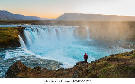 Fantastic summer morning view of the Godafoss Waterfall on Skjalfandafljot river. Man taking a photo standing on the edge of a cliff. Northeastern Region, Iceland, Europe. Visit Iceland. Beauty world.