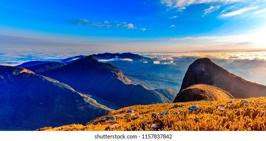 Fantastic sunrise over rocky mountain with view on misty valley. Mountain of fog. Mountain peaks. Sea of clouds. Pico Parana, Brazil. Orange and Teal.