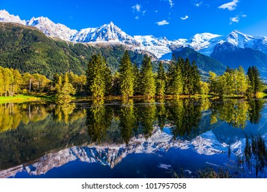 Fantastic sunset in the Alps. Snowy peaks of the Alps are reflected in the lake in mountain resort of Chamonix. The foot of Mont Blanc. Concept of active and ecotourism