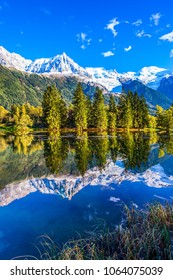 Fantastic sunset in the autumnal Alps. Stunning reflections of snowy peaks in the lake water. Mountain resort of Chamonix. Concept of active and ecotourism