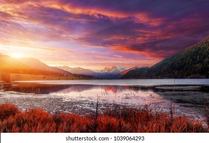 Fantastic sunset over the Famous lake Lago Della Muta. wonderful picturesque Scene with colorful Dramatic sky. Fishingparadise, Region Haidersee, Reschenpass, Bolzano, Italian Alps, Italy, Europe