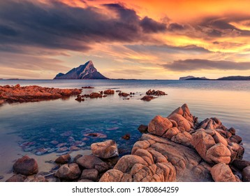 Fantastic sunset with Tavolara mountain on background. Astonishing summer seascape of Mediterranean Sea, Porto Taverna beach, Sardinia island, Italy, Europe. Beauty of nature concept background.