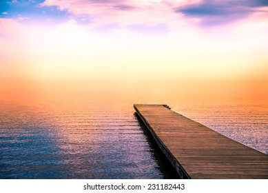 fantastic tranquil scene of a pier in the sea with fog and the sky above
