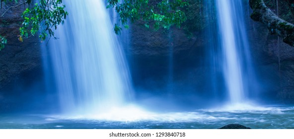 Fantastic tropical waterfall under the moonlight, gently water falling on the cliff, as a watercolor painting. Khao Yai National Park, Thailand. Long exposure.