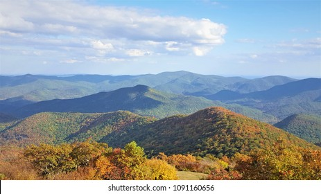 The fantastic view from Brasstown Bald mountain ( the highest mountain in Georgia) colorful in Fall season with white fluffy clouds and blue sky, North Georgia in USA.