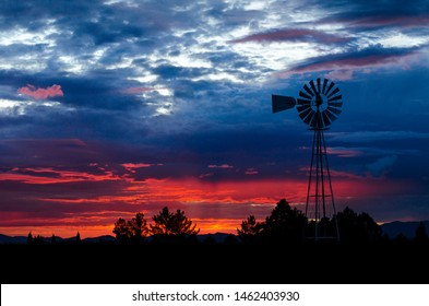 Fantastic view of dark overcast sky in rural setting. Dramatic and picturesque evening twilight sunset against windmill.