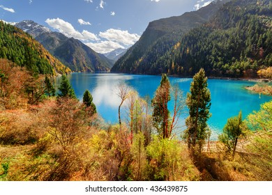 Fantastic view of the Long Lake with azure water among mountains and fall woods in Jiuzhaigou nature reserve (Jiuzhai Valley National Park), China. Beautiful snowy peaks are visible in background.