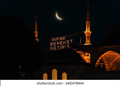 "Fantastic view with mahya among the Blue Mosque (Sultanahmet Camii) minarets and bright moon at the starry night. Text translation: ""Aid brings blessing"""