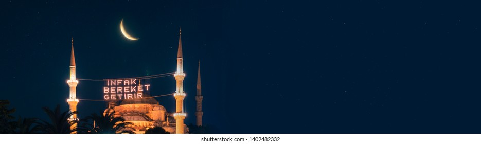 "Fantastic view with mahya (Text translation: ""Aid brings blessing."") among the Blue Mosque (Sultanahmet Camii) minarets and bright moon at the starry night with your text space."