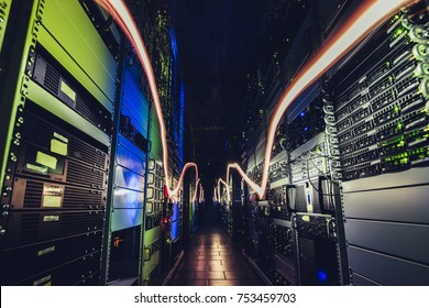 Fantastic view of the mainframe in the data center rows. Shot of a corridor in large working data center full of rack servers and supercomputers. Data centre interface.