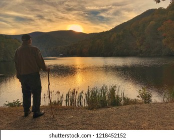 Fantastic view of a man watching sunset on the mountain with reflection in the lake at Vogel State park with blue sky and dramatic clouds on the background, Autumn in GA USA.