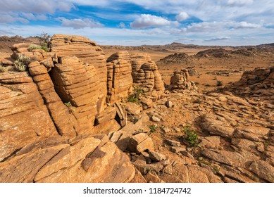 Fantastic view at rock formations and stacked stones on granite hilltops. Baga Gazriin Chuluu, Gobi desert, Mongolia.