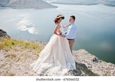 Fantastic wedding couple standing on the edge of rocky precipice with a perfect view of lake on the background.