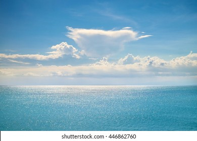 Fantastic white clouds on blue sky horizon. Calm ocean with sunlight reflection, Bali. Sunny sky clouds above blue ocean surface. Vibrant sunny sea and clouds. Tranquil Bali serenity of amazing ocean