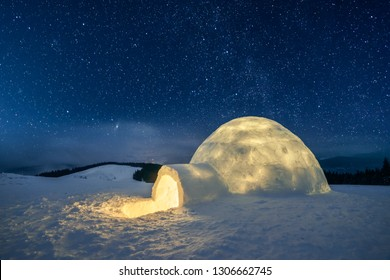 Fantastic winter landscape glowing by star light. Wintry scene with snowy igloo and milky way in night sky