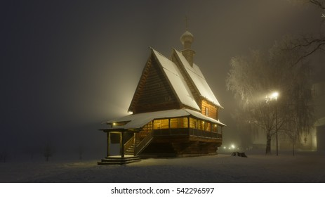 Fantastic winter landscape. Heavy fog in the evening. The wooden Nikolskaya Church in Suzdal Kremlin, Russia.
