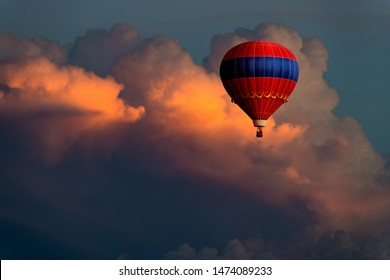 Fantastical image of an ornate red and blue hot air balloon floating high in beautiful storm clouds glowing in purple, pink, yellow, and orange colors at sunset