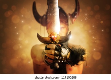 Fantastical portrait of a warrior with focus on powerful sword with skull against magical background of rays of light
