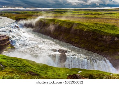 Fantastically powerful and picturesque waterfall in Iceland - Gullfoss. Huge masses of water crash into the abyss. Water fog fly up over falls. The concept of extreme and phototour