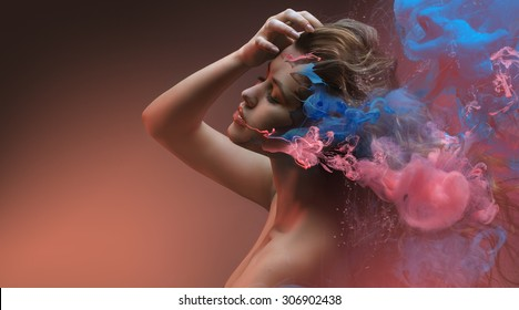 Fantasy beauty fashion model face closeup inside colorful paint in shape of abstract clouds. Design with Water color spreading underwater. Fantastic shapes in orange background.