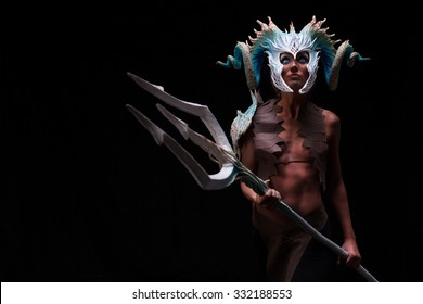 fantasy concept, of a young girl, warior strong, brave, muscular wearing a helmet - mask with horns on head with coral white with dots, and see creatures patterns, holding large trident in hand,