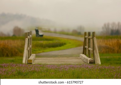A fantasy fairy bridge with purple flowers in the foreground and a bench on a trail in the fog in the background.