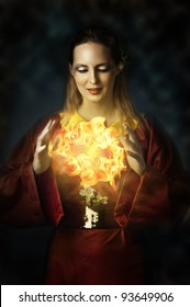 Fantasy fairytale world - portrait of young beautiful woman - fairy, witch, elf or wizard. She making magic - casting fire ball