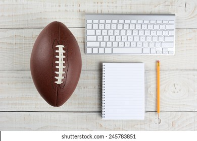 Fantasy Football Draft still life. A computer keyboard, pad and pencil and an American style football on a white wood table in a home office.