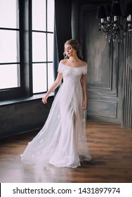 fantasy gentle young beautyful princess long white dress open shoulders. dark black room medieal Gothic style fabulous bridal woman fly vintage clothes gown window glamour style lady mysterious castle