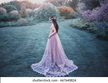 Fantasy girl in a fairy garden. Young elf in a beautiful purple dress with a long train. Creative colors artistic processing