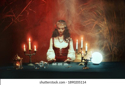 Fantasy girl in image of gypsy witch sits at table in dark gothic room. Art Red costume. Fortune teller magical woman reading future on tarot cards, crystal ball. Ritual candles burning seance, smoke