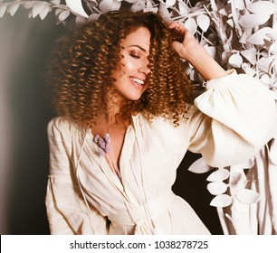 Fantasy Girl with long blonde blowing curly hair. Spring or summer beauty teen girl with flowers. Beauty Makeup and Nai Art Concept. Beautiful fashion model woman with soft makeup, perfect skin,curls
