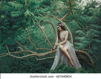 Fantasy girl in spring garden. young princess in purple lace dress sits on a tree green branch. Creative colors artistic processing photography. Long bare sexy legs, pretty cute attractive face