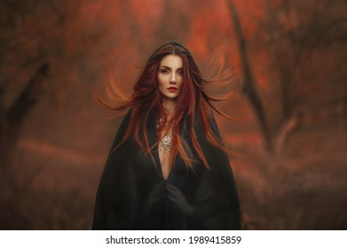 fantasy gothic woman dark witch. Red-haired evil Girl demon in black dress cape hood. Long hair flutters fly in wind. Dark dense deep autumn forest orange colors trees. Medieval dress, silk clothes.