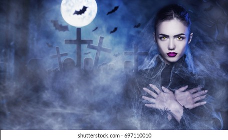 Fantasy Halloween Vampire woman portrait. Beauty Sexy Vampire in a cemetery, at night wearing spider web. Hands on chest. Fashion Art design. Beautiful Gothic model girl. Dark Elf. Cat's eyes