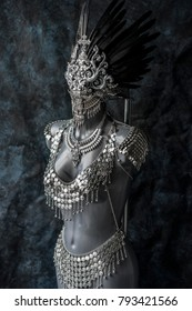 Fantasy, handmade piece, silver jewelry costume with chains and coins. wears a headdress made with feathers and gothic pieces