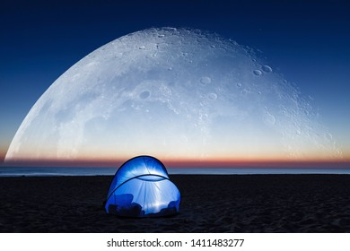 Fantasy image of dawn on the beach, super big moon over the sea and lit tent