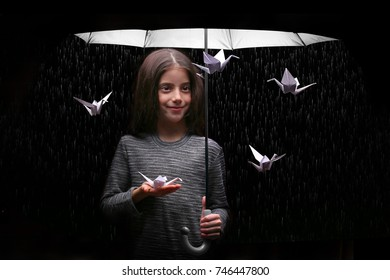 Fantasy image with girl under umbrella and origami birds