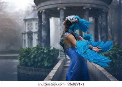 Fantasy image and stories, Beautiful young woman with dress made of blue feathers, angel fallen from heaven to earth.