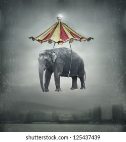 Fantasy image that represent a flying elephant with circus tent in the sky and landscape on the background